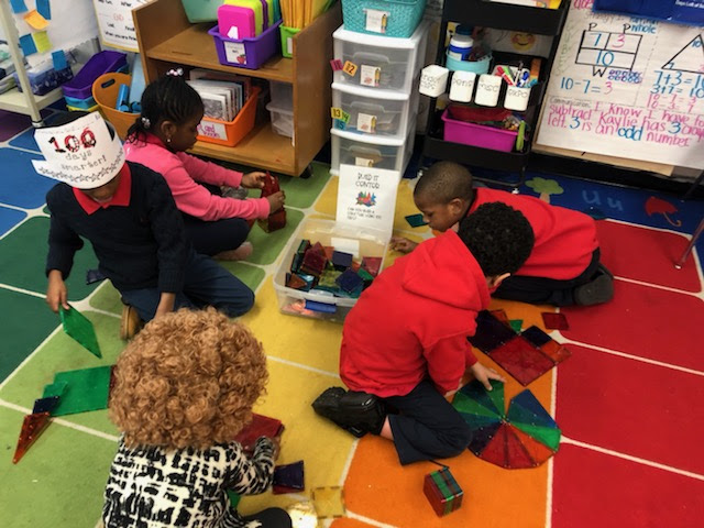 Students building structures on the class rug.