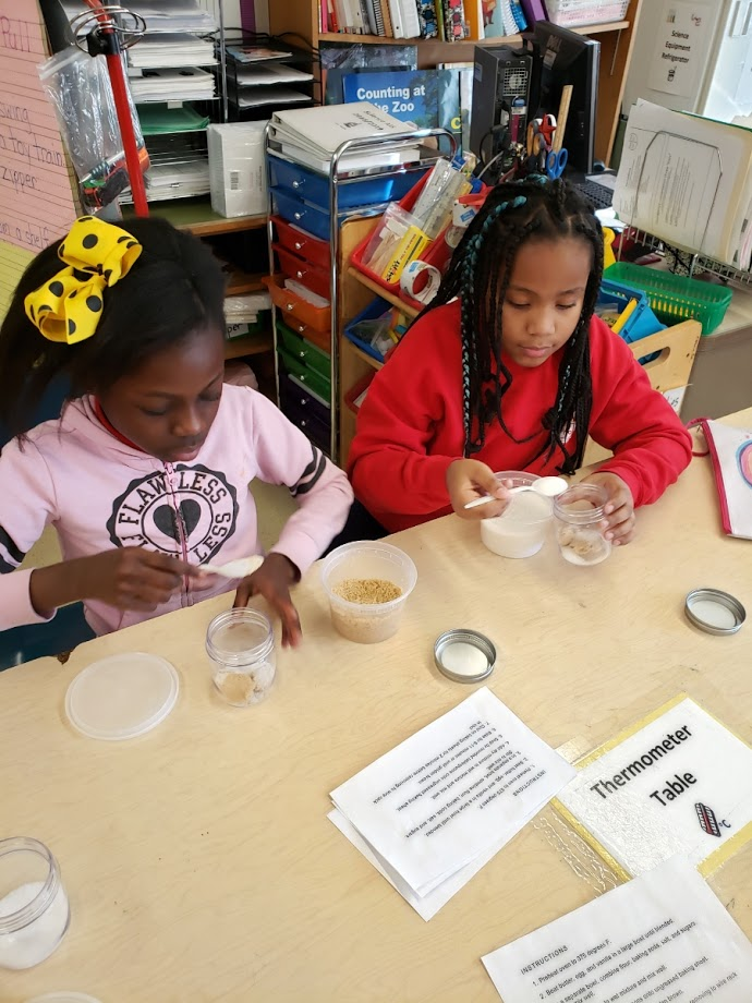 Two female students measuring ingredients for a recipe.