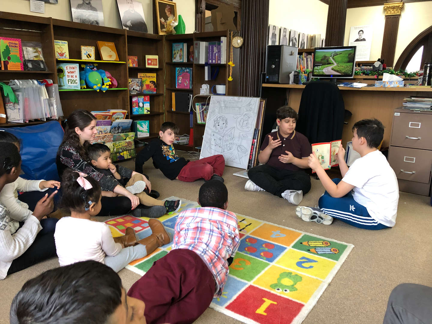 students gathered together as one reads a story to the group