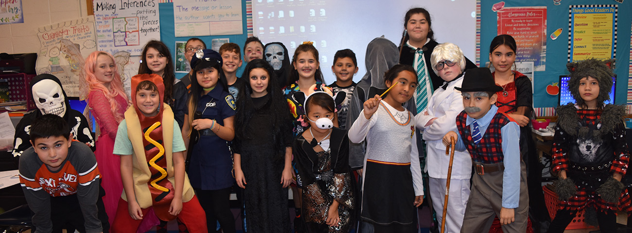 20 kids in class pose in halloween costumes