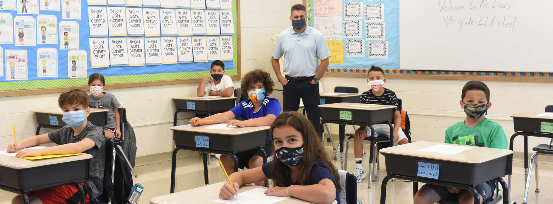 male teacher stands with his fourth grade class