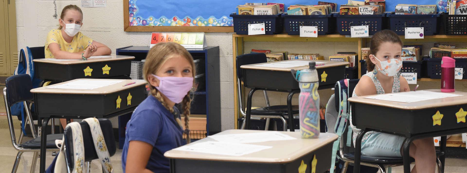 three girls with masks sit in desks