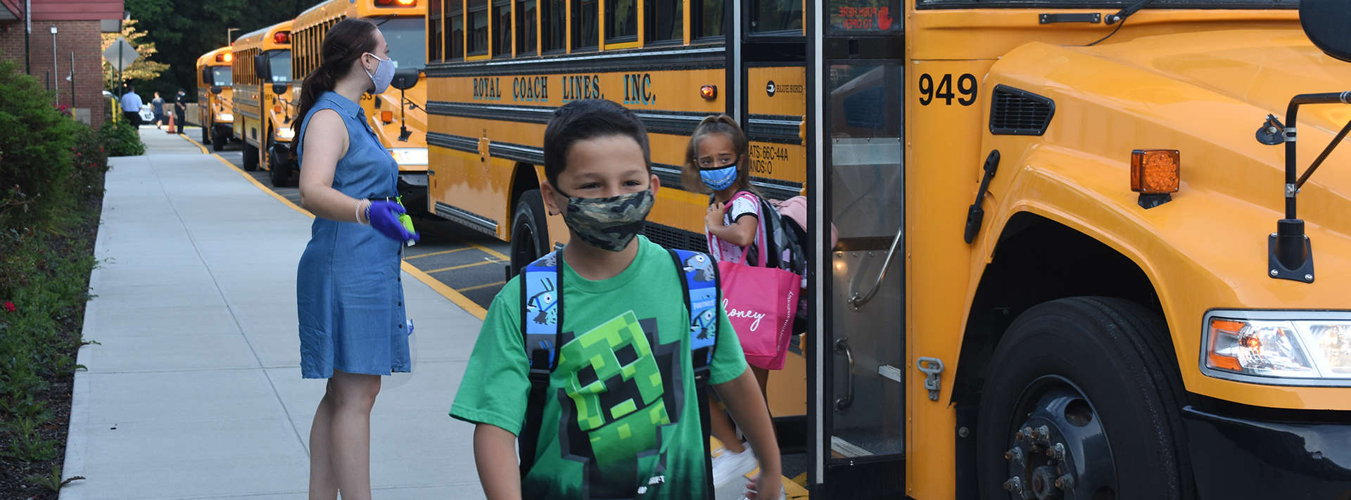 boy with mask exits the.bus