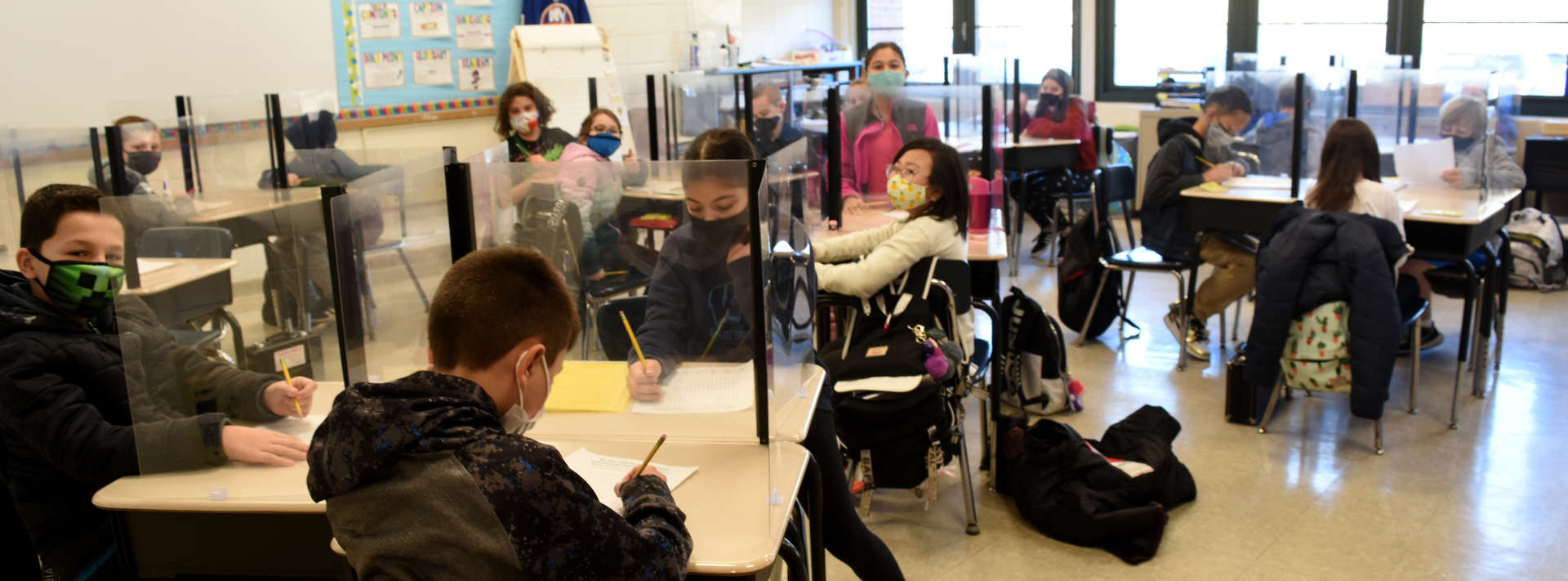 4th grade students wearing masks sitting at desks with barriers