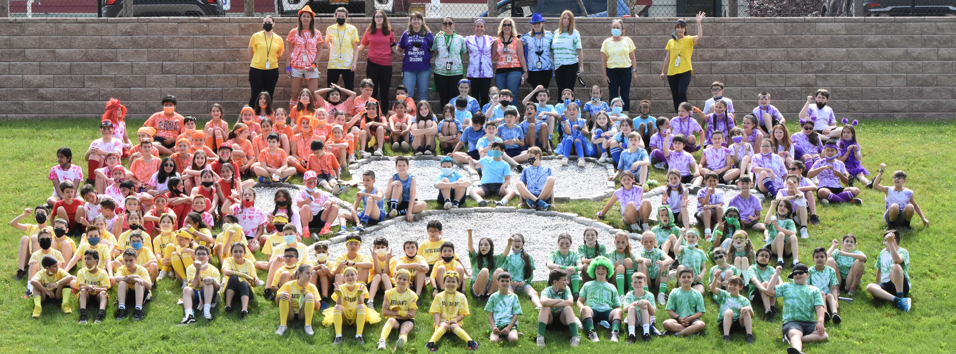 Entire 5th grade wearing colorful shirts sit on grass in front of school.