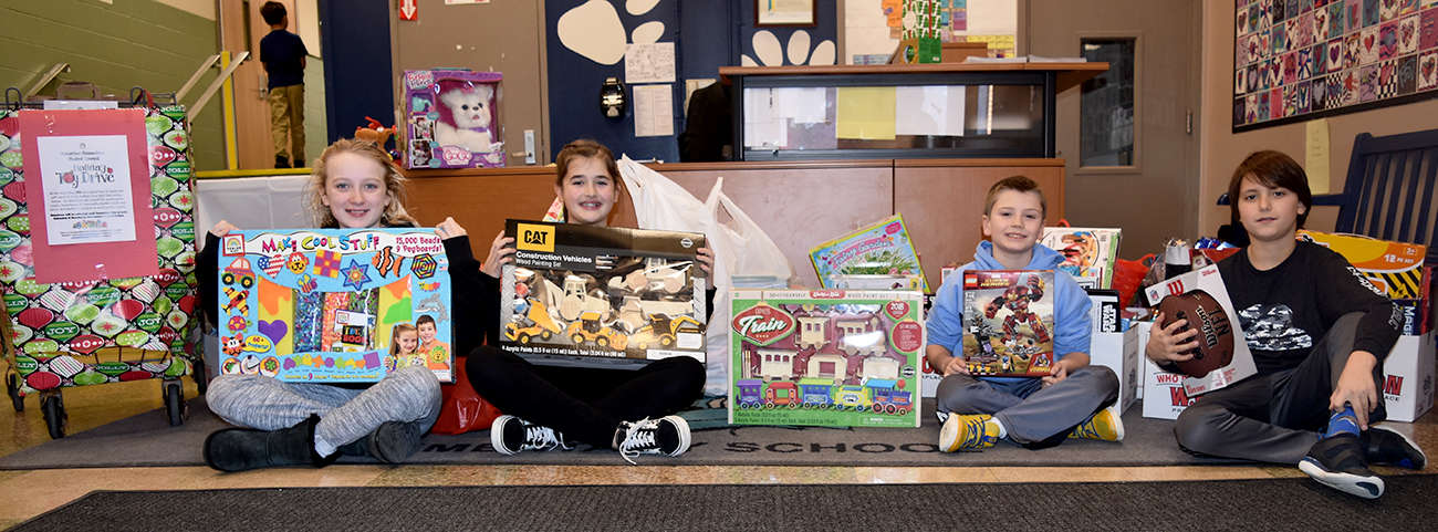 4 students sit with gifts collected for needy children