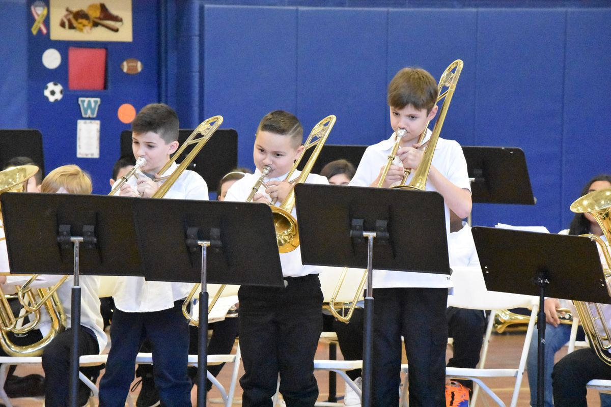 Kids playing trombone in band concert