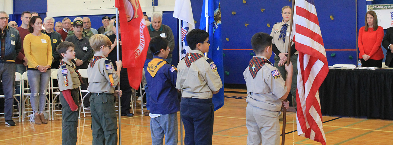 5 boys scouts stand in front of the American flag.