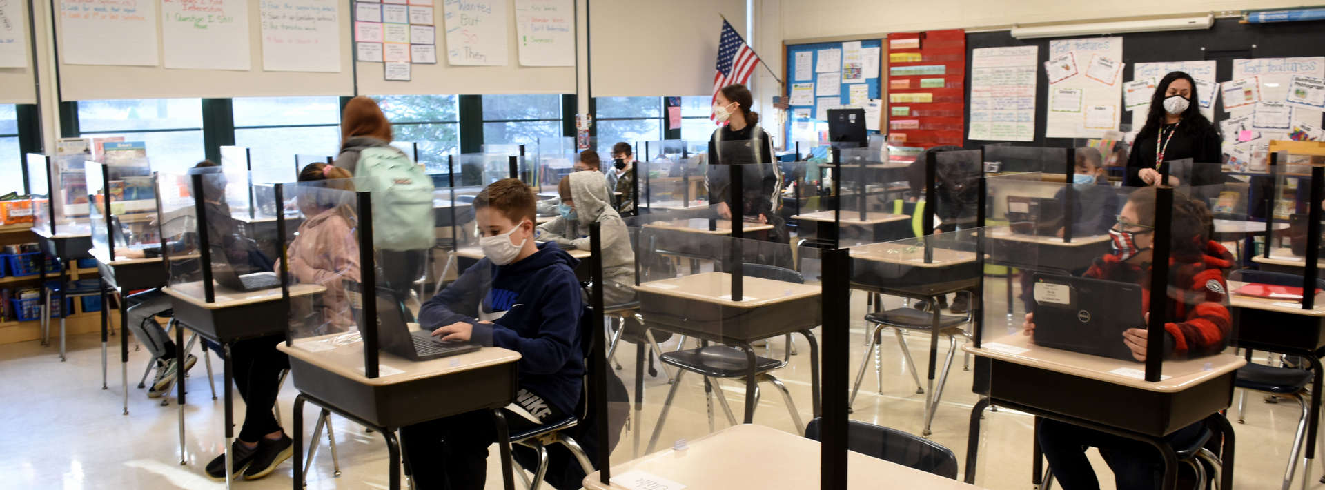 Students with masks sitting at desks with barriers