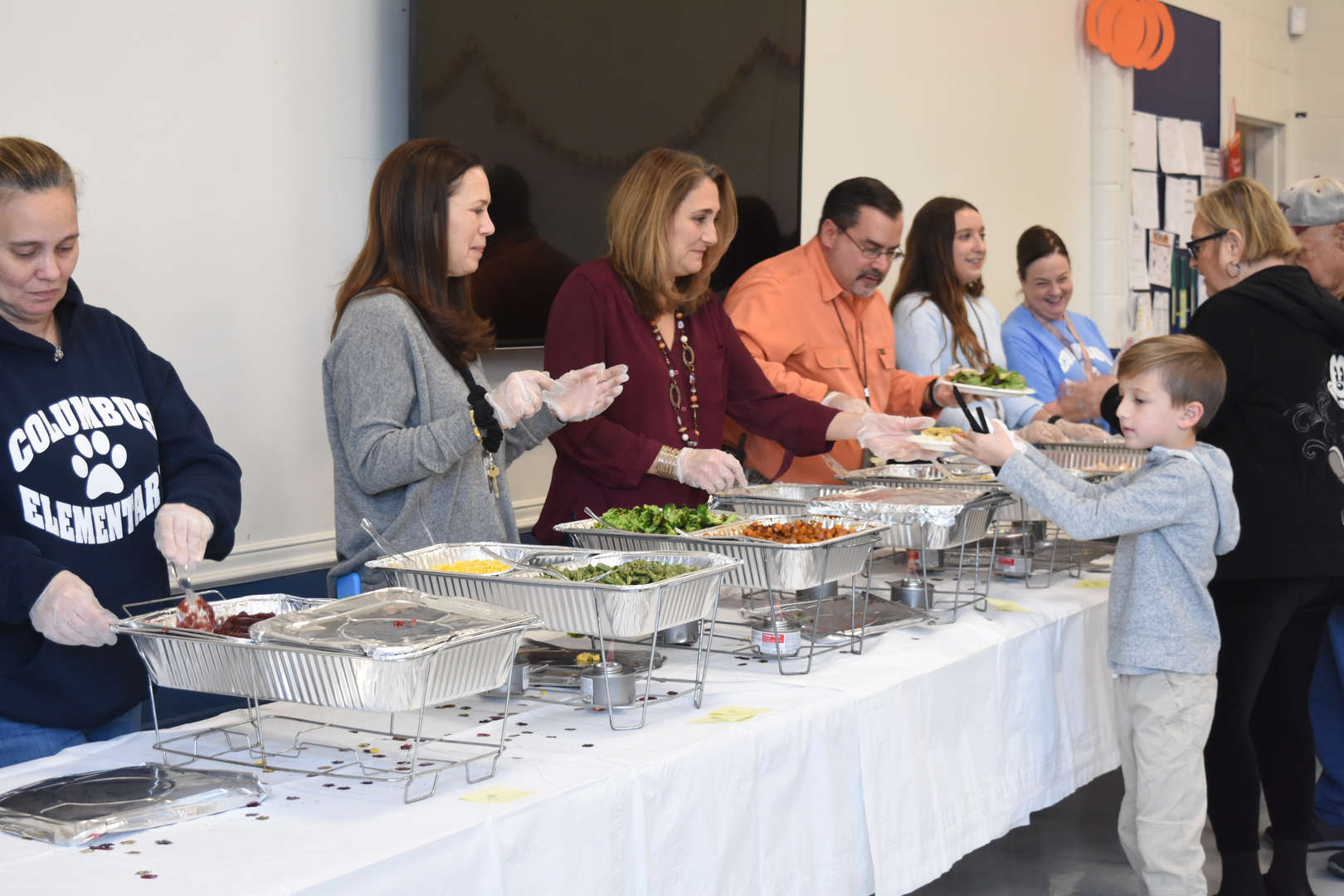 6 adults serve thanksgiving meal from buffet line