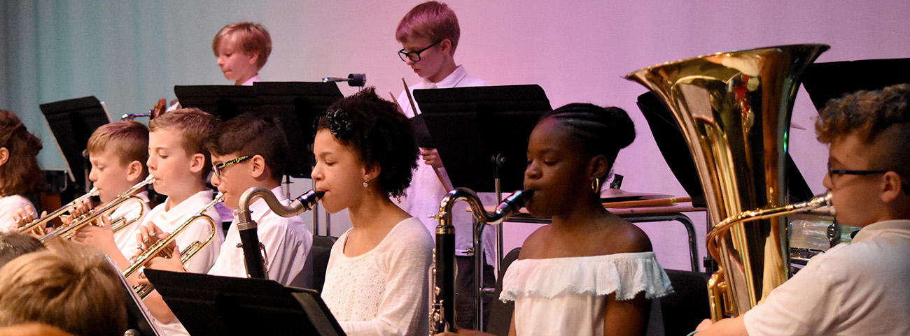 Kids play instruments in band concert