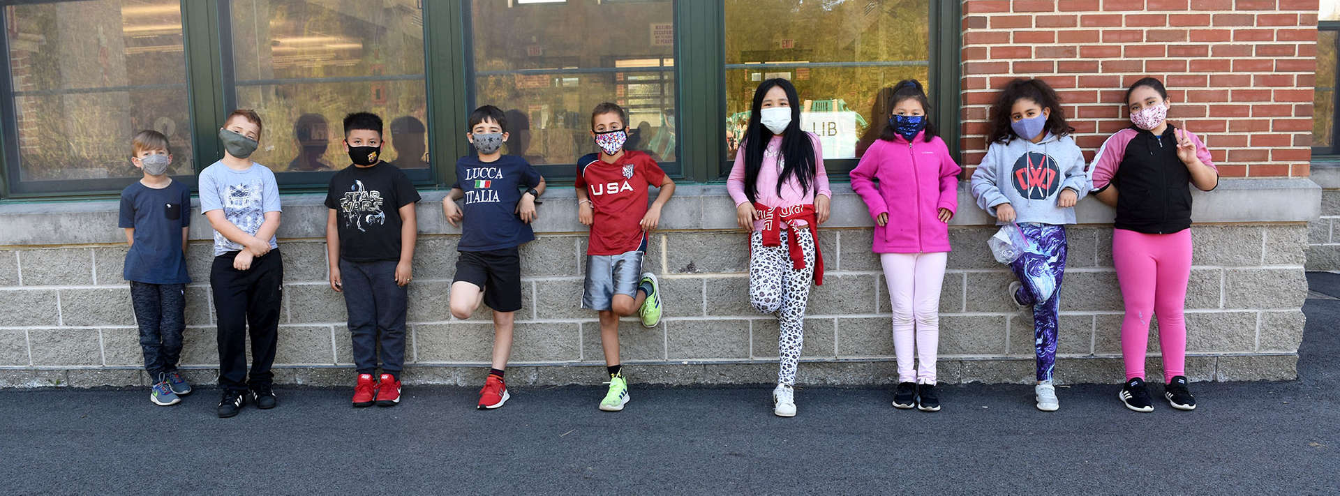 boys and girls with masks line up along the wall at recess