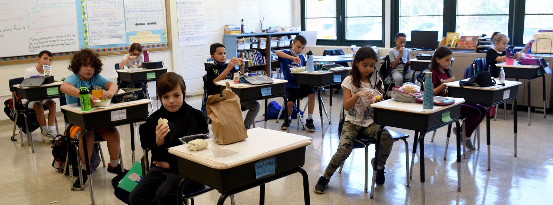 students sit at desks eating their lunch