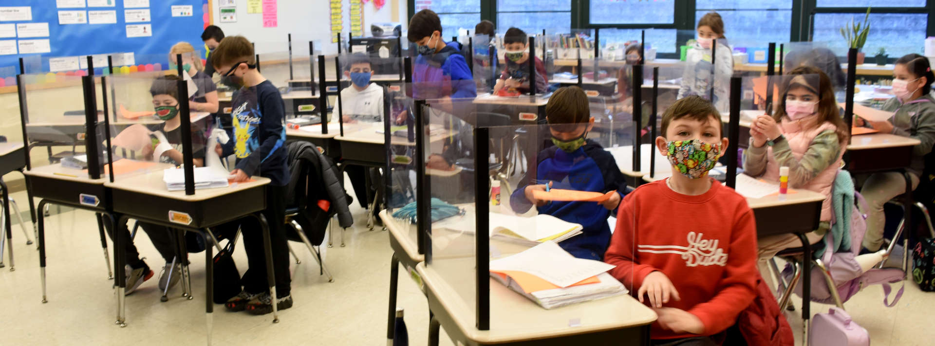 3rd Grade students wearing masks sitting at desks with barriers