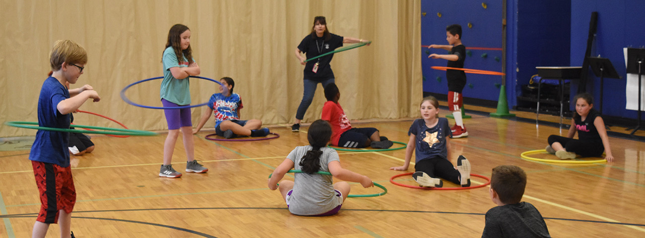 Group of students hula hoop with teacher.