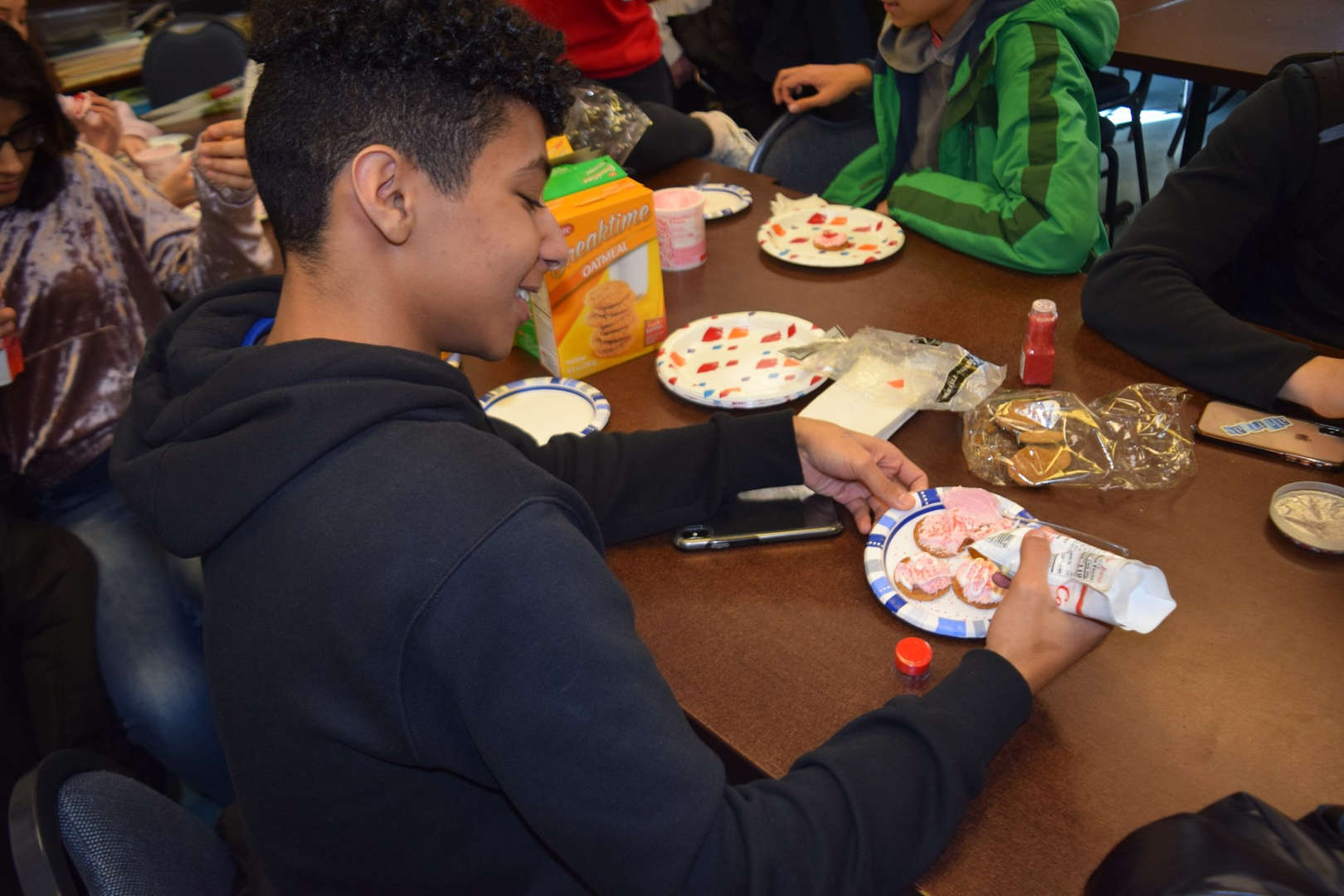 Academy students decorate and eat cookies together for No One Eats Alone Day