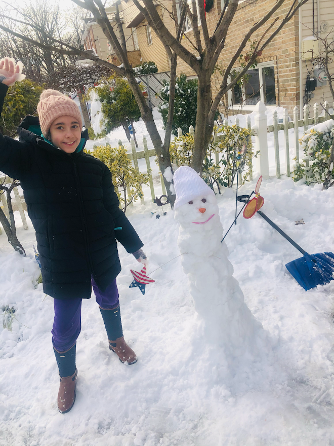 a girl is standing next to the snowman she made in her yard