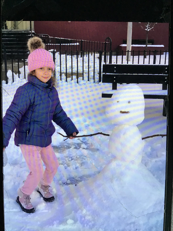 young girl is adding stick arm to her snowman
