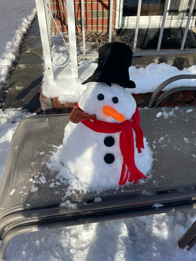 Snowman on the sidewalk. With a red scarf, carrot nose , black button eyes