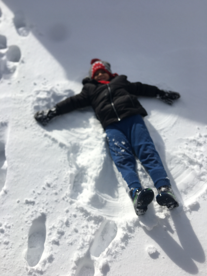 a boy is making a snow angel in his yard