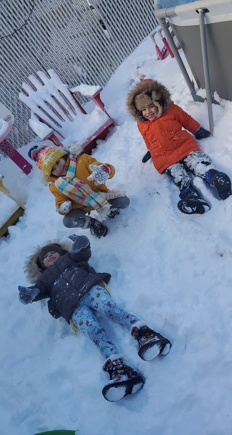 three children are making snow angels in the snow