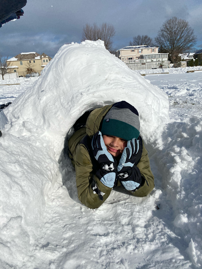 boy has made an igloo in his front yard with snow and is crawling out