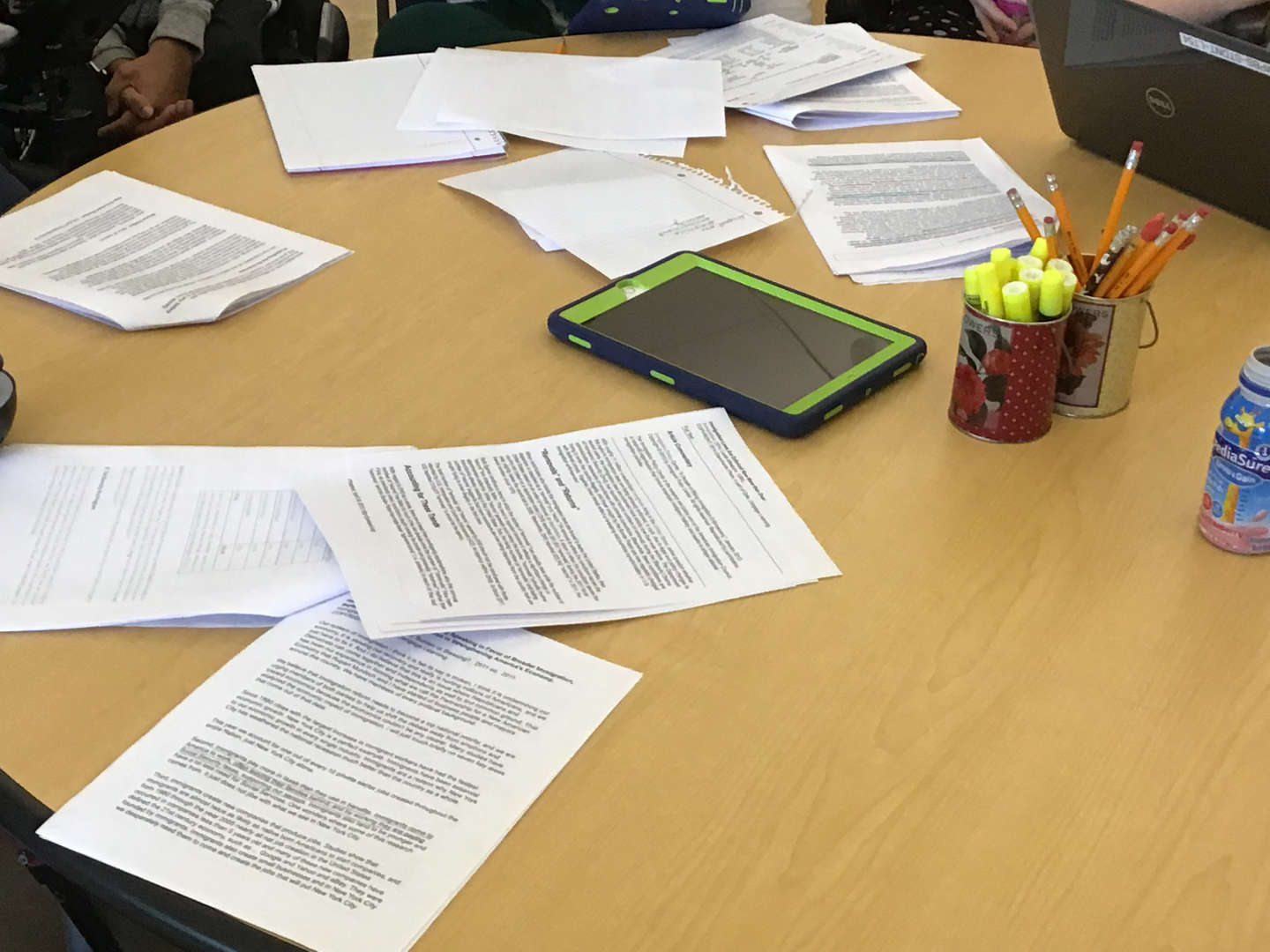 Written resources, highlighters and an iPad on a table.