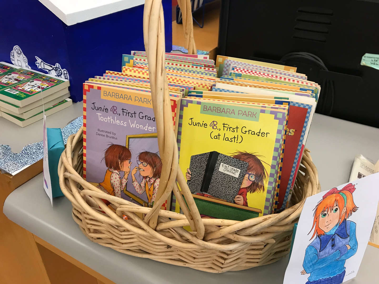 A paperback book series in a basket on a table.