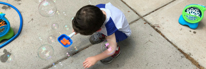 Student playing with bubbles outside