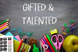 Gifted and talented logo on a chalkboard with school supplies