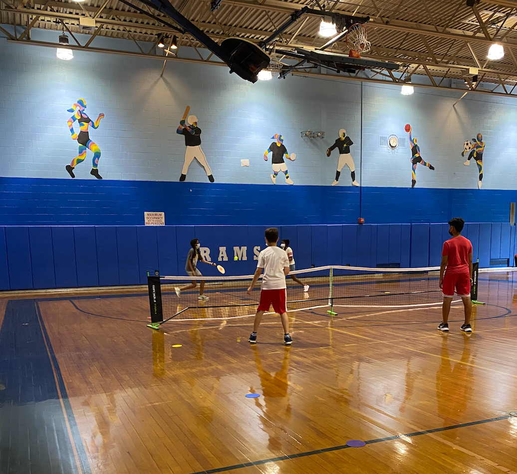 Students playing volleyball in a gym