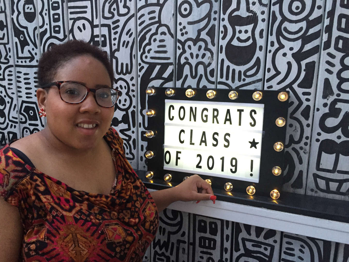 "Student with a ""Congrats Class of 2019"" sign"