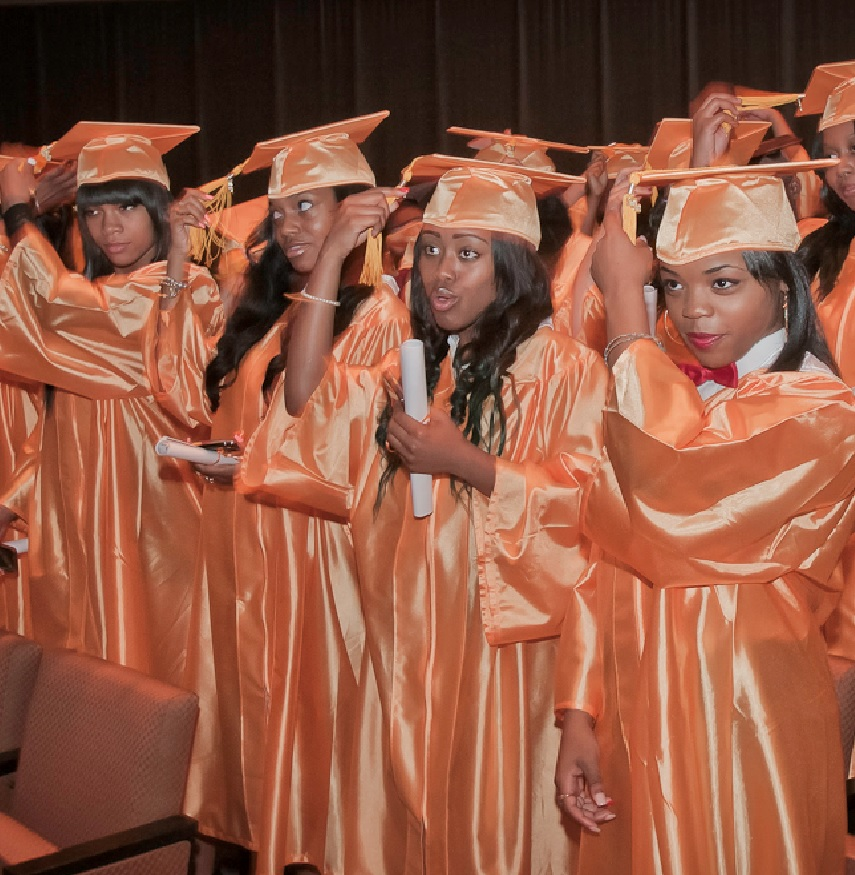 New Dawn Charter High School graduates in orange caps and gowns