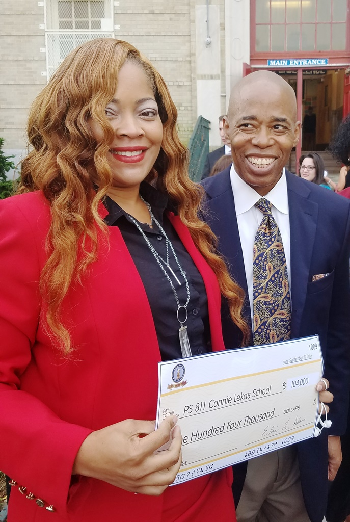 Brooklyn Borough President, Eric Adams presents a check for $104,000 to The Conie Lekas School, P811K. Accepting the check on behalf of the school is Antoinette Rose, Principal.