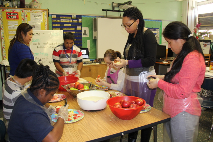 Students in cooking class cutting vegetables