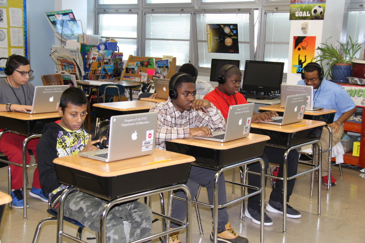 3 students using macbook pros in a classroom