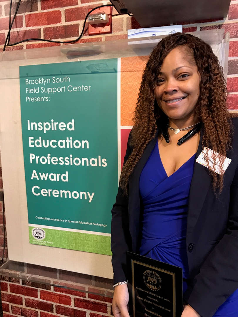 Principal Rose in front of professionals award ceremony poster.