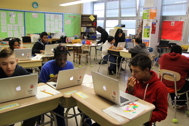 A group of students in a classroom using MacBook Pro laptops.