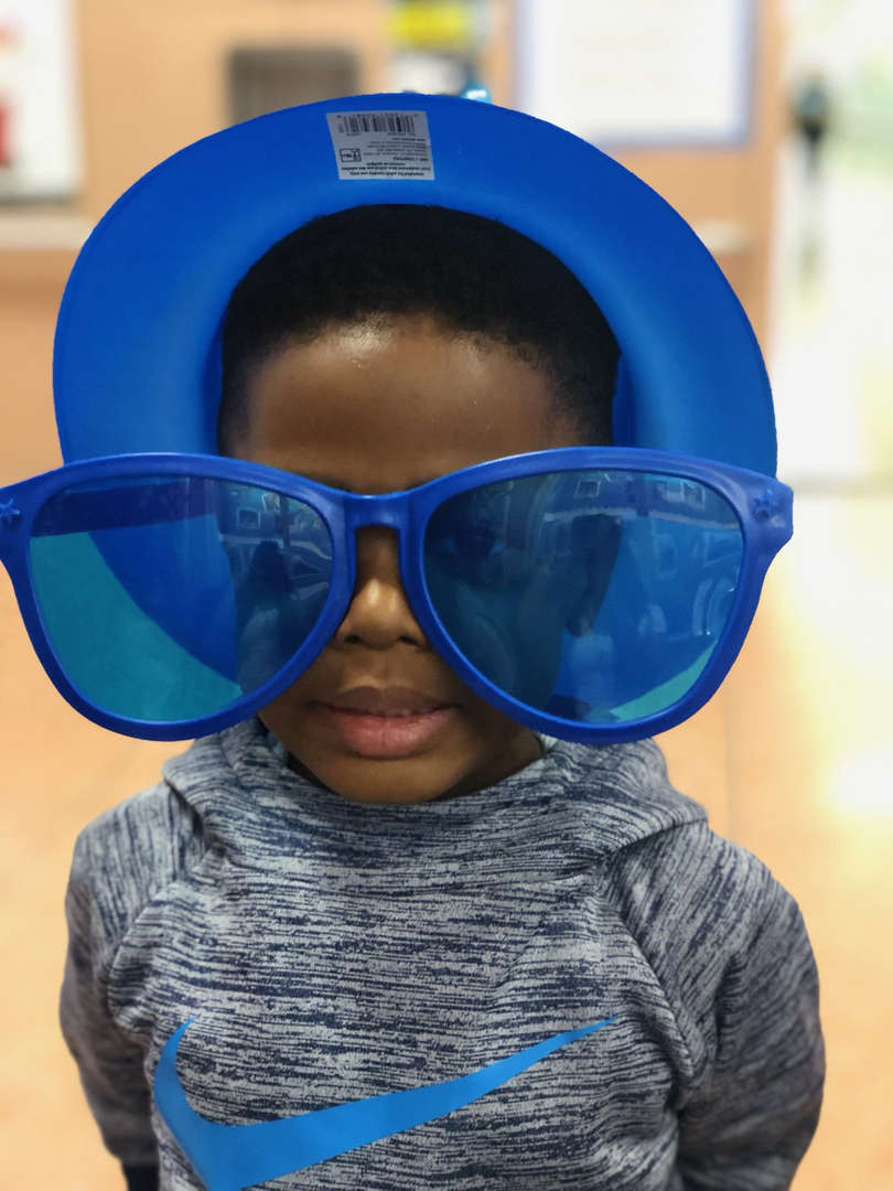 Kid wearing an oversize bleu sun glasses.