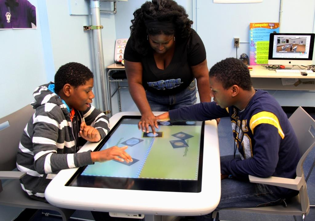 Two students and a teacher using a smart table