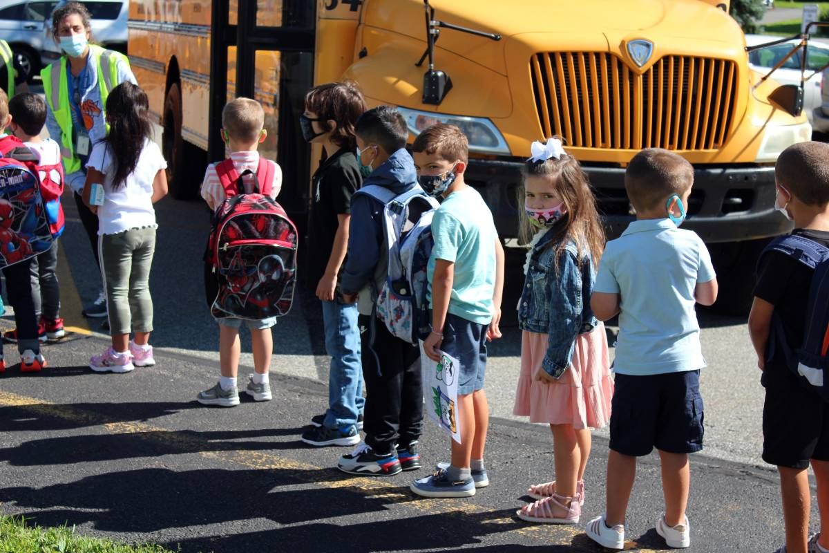 Kindergarteners wait in line to board a school bus on the first day