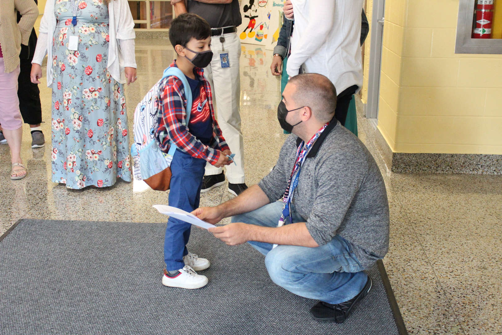Staff member assists a student on the first day of school