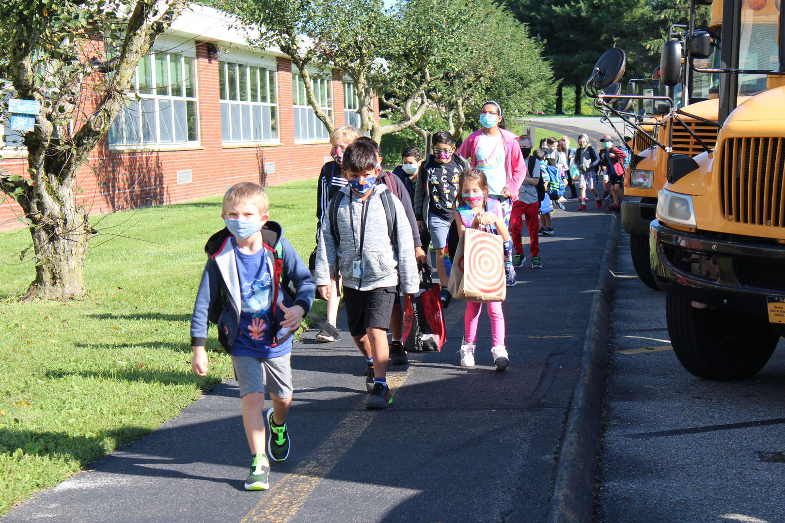 Students enter Kent Primary from the bus on the first day of school