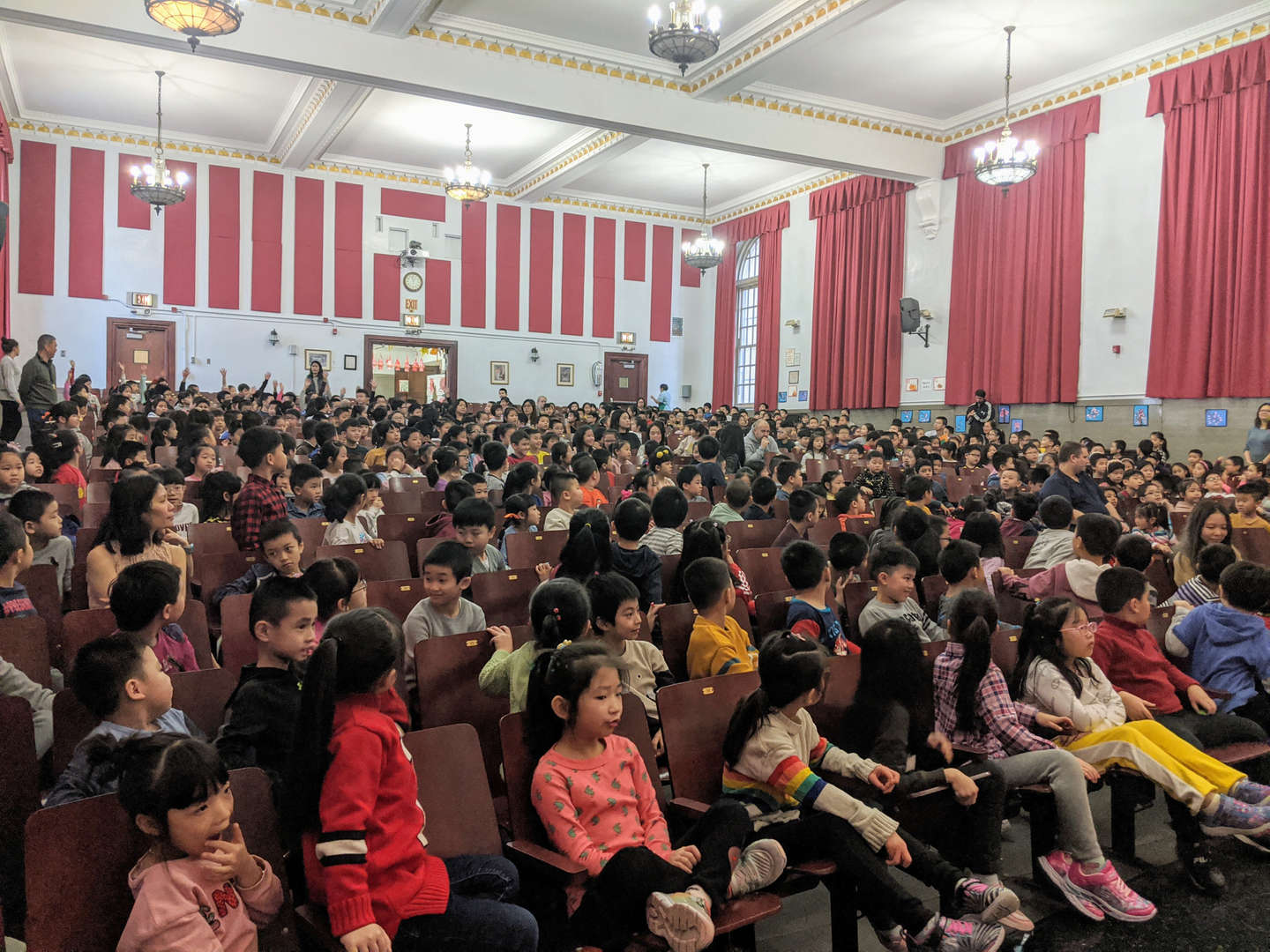 Students waiting in the school auditorium.