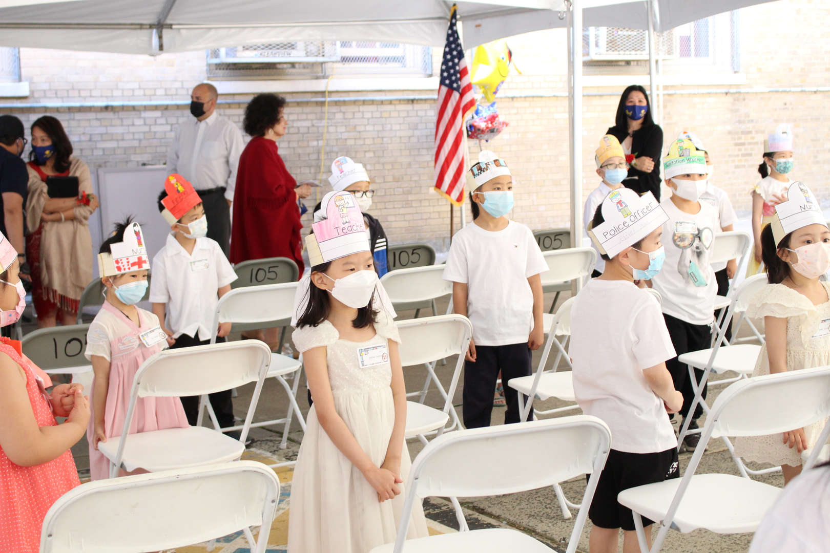 Kindergarten students face their parents and wave to them.