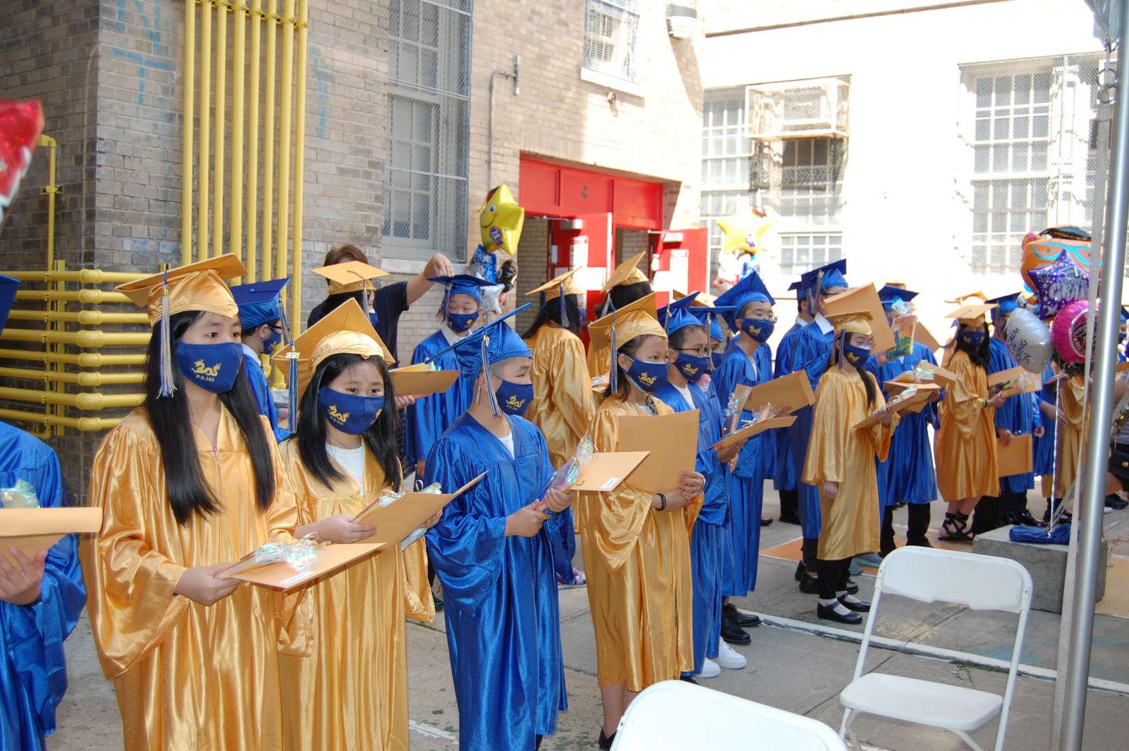 Graduates holding their diplomas.