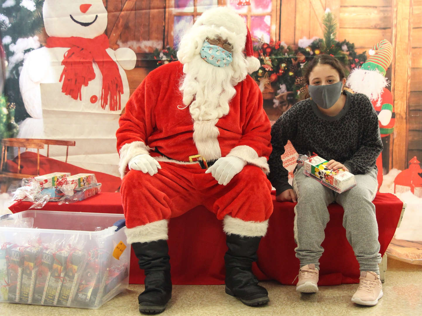 Santa makes a young girl smile with a gift.