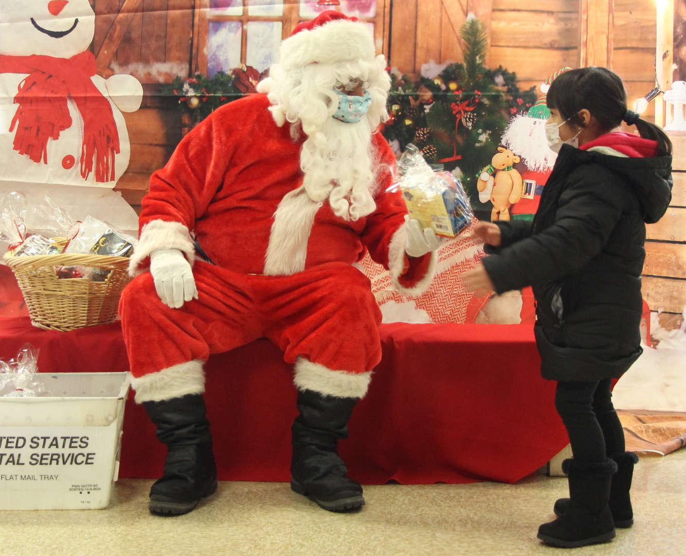 Santa gives a present to a student.
