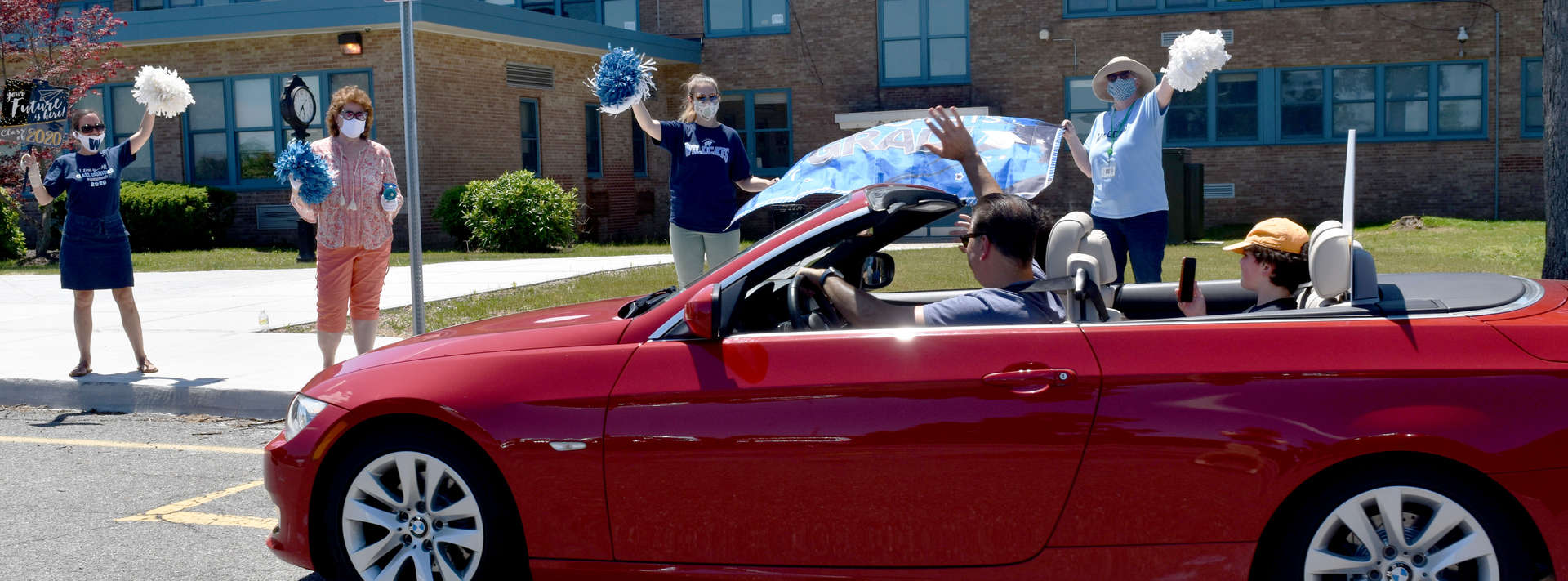 red convertible drives by waving teachers