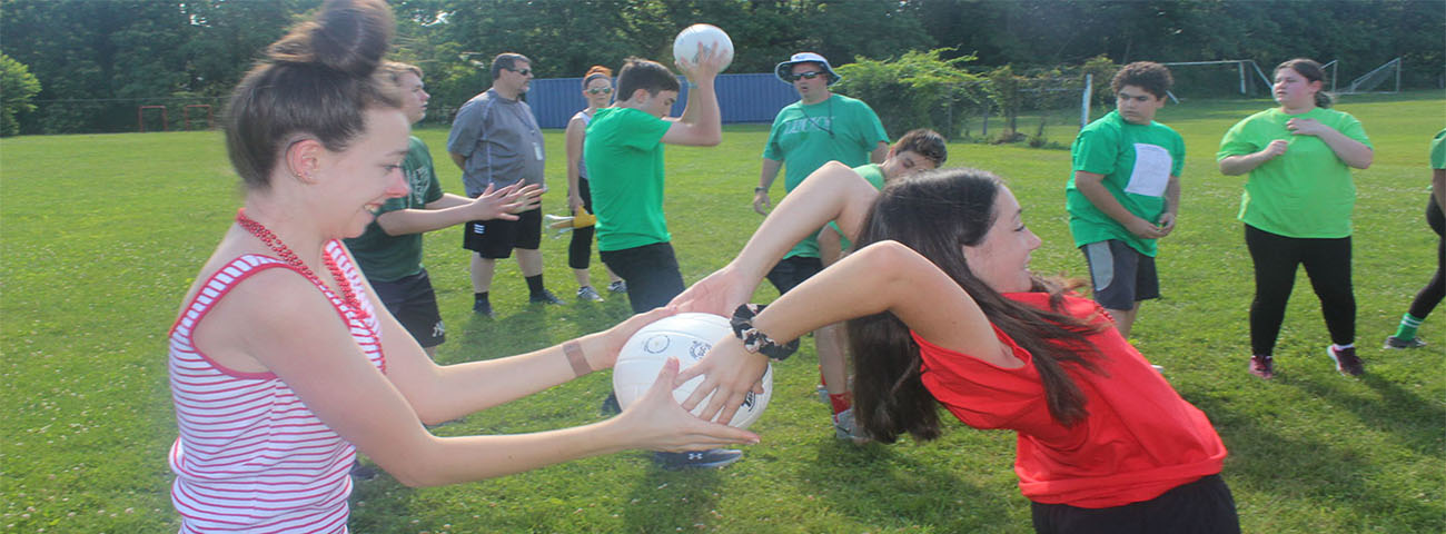 Eighth Graders enjoying Field Day playing Over and Under.